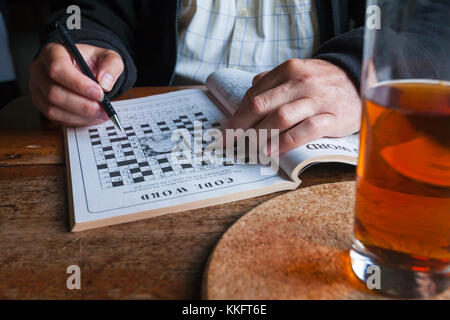 Man doing code word crossword in puzzle book with glass of drink - just hands showing - Stock Photo