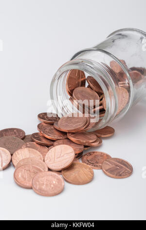 UK copper pennies cascading from mouth of glass jam jar - metaphor for saving pennies / money, kitchen table issues, - Stock Photo