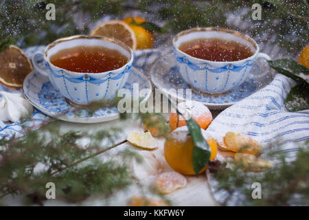 Beautiful christmas card. The morning of the New Year - tea and tangerines, powdered with powdered sugar. - Stock Photo