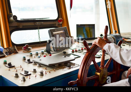 Close view into captain's cabine, navigation equipment and captain's hand on rudder during cruising - Stock Photo