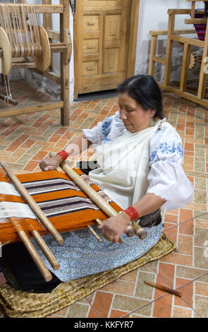 Ecuador culture - an indigenous middle aged woman weaving using a traditional back strap loom, Otavalo, northern - Stock Photo
