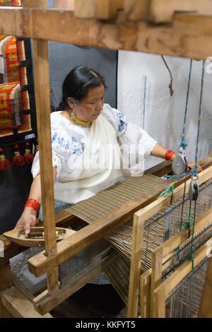 Ecuador Culture - an ecuadorian mature woman using a traditional loom to make textiles, Otavalo, Ecuador, South - Stock Photo