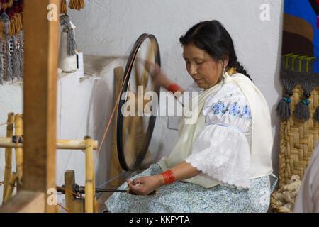 Ecuador Culture - an ecuadorian mature woman using a traditional spinning wheel spinning yarn to make textiles, - Stock Photo