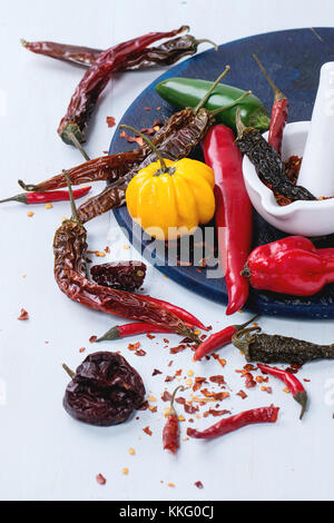 Assortment of fresh, dryed and flakes hot chili peppers with white ceramic mortar on dark blue cutting board over - Stock Photo