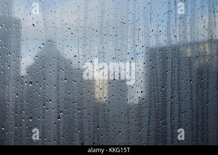 close-up of water droplets on window with buildings and blue sky and clouds in background - Stock Photo