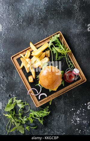 Homemade traditional hamburger with beef, tomato, cheese, aragula, served on wooden slate serving board with french - Stock Photo