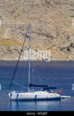 Yacht moored off the coast of Symi Island in the Dodecanese, Greece - Stock Photo
