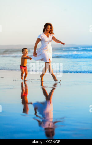 Happy family holiday - mother, baby son have fun together, barefoot child run by water pool along sunset sea surf - Stock Photo