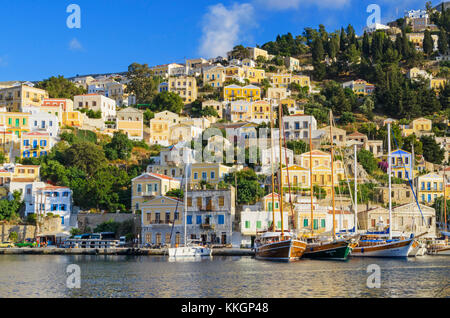 Boats moored along the scenic waterfront of Yialos Town, on the island of Symi, Dodecanese, Greece - Stock Photo