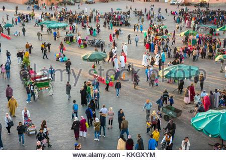 Morocco, Marrakech-Safi (Marrakesh-Tensift-El Haouz) region, Marrakesh. Crowds of people walk across Jamaa El-Fna - Stock Photo