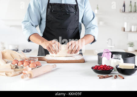 A cook with eggs on a rustic kitchen against the background of men's hands - Stock Photo