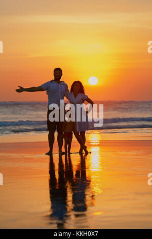 Happy full family - young father, mother, baby son have fun together on sand beach with sea surf on sunset sky with - Stock Photo