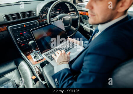 Focusing on work. businessman working on laptop while sitting on back seat car - Stock Photo