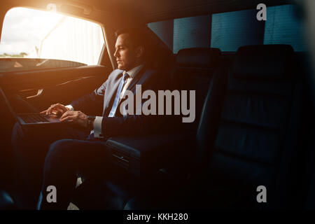 Serious businessman in a car with laptop - Stock Photo