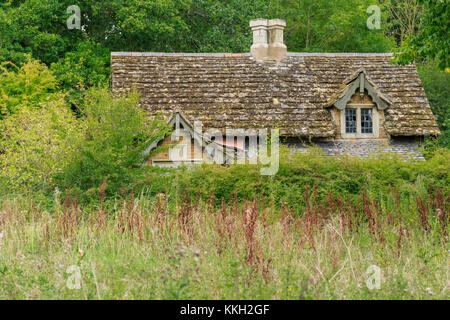 Derelict cottage in the wood and overgrown garden - Stock Photo
