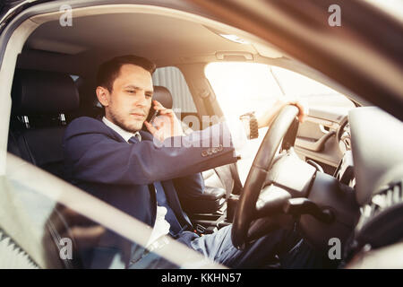 Handsome businessman talking with phone sitting with laptop on backseat of car - Stock Photo