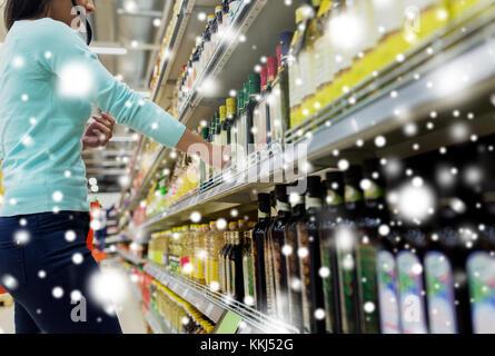customer choosing olive oil at supermarket - Stock Photo