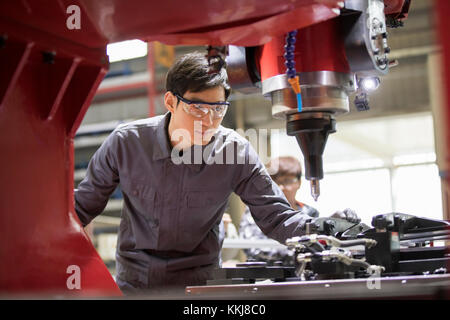 Confident Chinese engineer working in the factory - Stock Photo