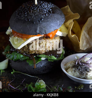 Lamb burger served with in a black bread bun at the Mute restaurant in Riga, Latvia. The burger features a slice - Stock Photo