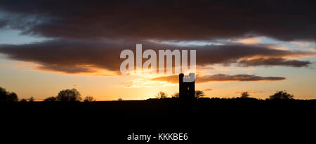 Broadway Tower silhouette at sunset along the cotswold way in late autumn. Broadway, Cotswolds, Worcestershire, - Stock Photo