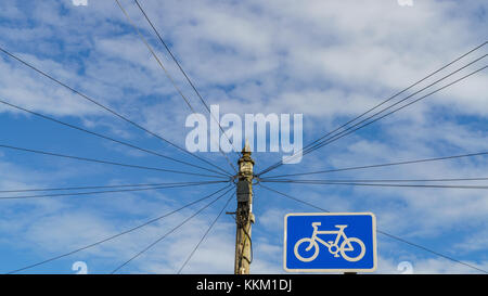 Power cables and power pole with bycicle sign, Exmouth, Devon, England, UK - Stock Photo
