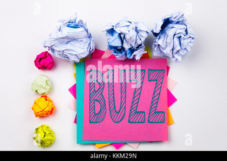 Writing text showing Buzz written on sticky note in office with screw paper balls. Business concept for Buzz Word - Stock Photo