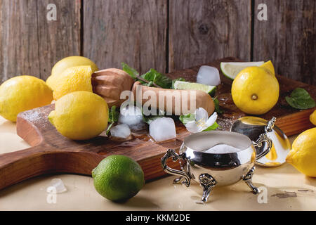 Heap of whole and sliced lemons, limes and mint with citrus reamer, sugar and ice cubes on little wooden cutting - Stock Photo