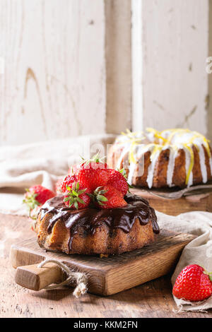 Homemade chocolate cakes with strawberries and dark chocolate ganache, and white frosting and lemon zest, served - Stock Photo