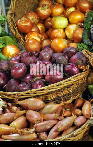 A selection of red onions, brown onions and shallots displayed in rustic baskets on a fruit and vegetable stall - Stock Photo
