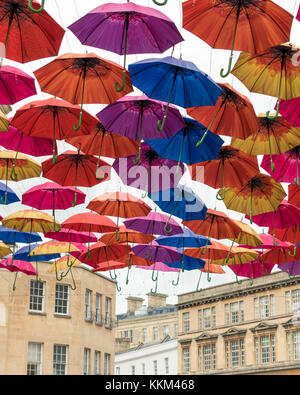 Open umbrellas hanging from wires above the shopping centre of the Southgate area of the city of Bath.