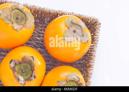 Fresh natural kaki fruits in the basket on white background - Stock Photo