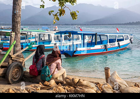 Two Indonesian women waiting for the ferry to the island Lombok at Gili Air, one of the Gili Islands in Indonesia - Stock Photo