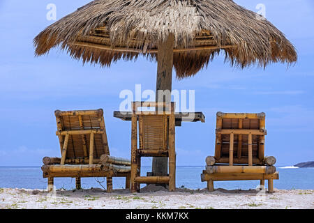 Relaxing bamboo deck chairs with parasol on white sandy beach looking towards ocean at Pantai Tanjung Aan on the - Stock Photo
