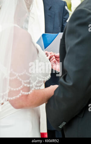 Close up view of bride and groom holding wedding rings  during wedding vows exchange at ceremony - Stock Photo