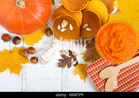 Golden tasty useful pumpkin pancakes, puree of a pumpkin on a white background. Autumn collection. - Stock Photo