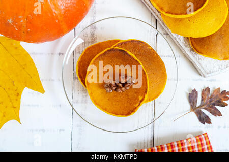 Fragrant golden pumpkin pancakes on a white wooden background. Top view. American traditional dish. - Stock Photo