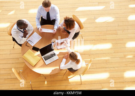 Four business colleagues in a team meeting, aerial view - Stock Photo