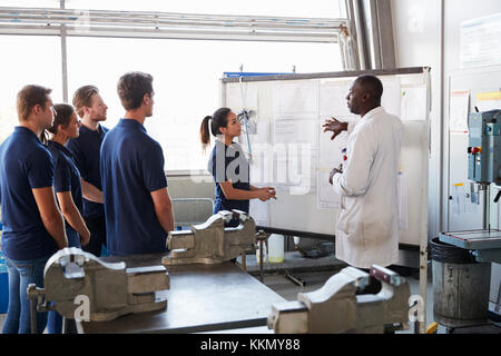 Engineer and female apprentice presenting at whiteboard - Stock Photo