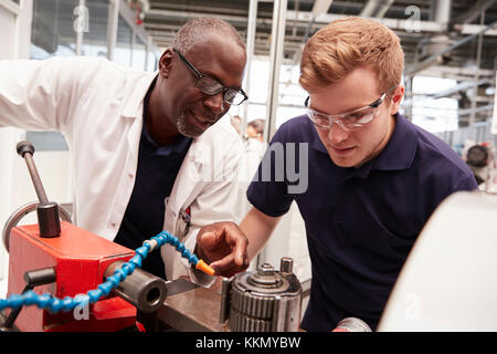 Engineer advising apprentice in factory, front view close up - Stock Photo