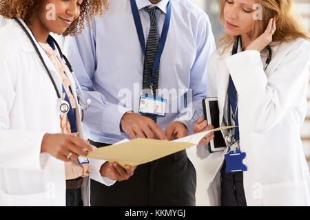 Three young male and female doctors consulting, mid section - Stock Photo