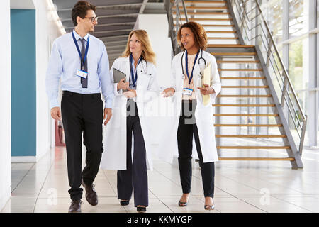Three young male and female doctors walking in hospital - Stock Photo