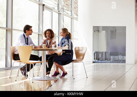 Three senior healthcare workers in a meeting, low angle - Stock Photo