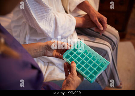 Nurse Helping Senior Woman To Organize Medication On Home Visit - Stock Photo