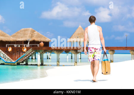 Man walking by the shore in the beach going away to a jetty with bungalows. He is wearing a colorful bathing suit - Stock Photo