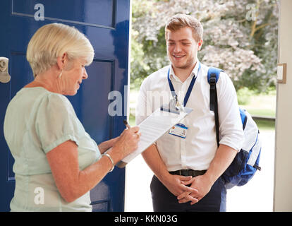 Senior woman filling in survey for visitor at her front door - Stock Photo