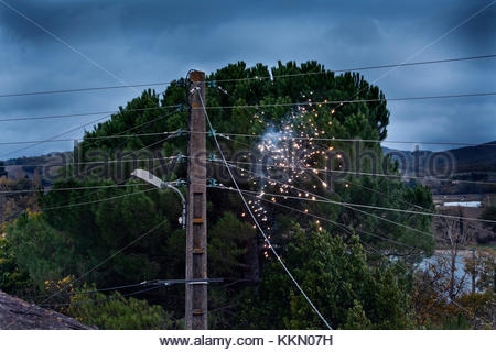 electrical short with sparks on a above the ground residential electrical wire distribution network France - Stock Photo