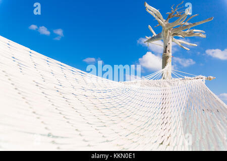 Hammock hold by a white tree in a shallow and clear sea on the lagoon in Maldives. - Stock Photo