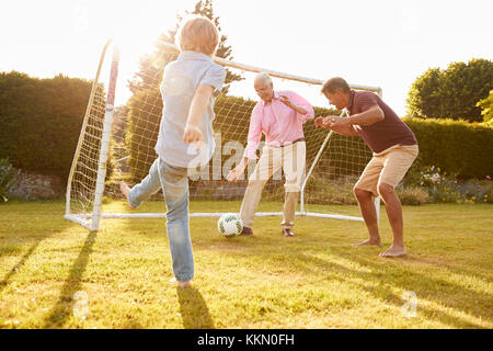 Three male generations of a family playing football - Stock Photo