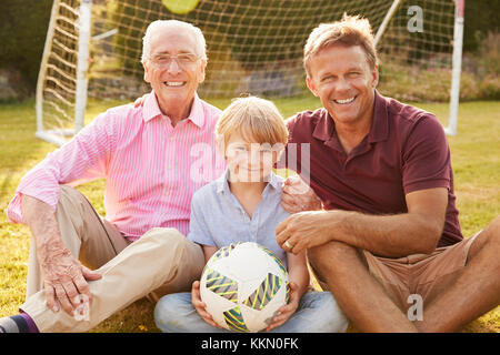 Three male generations of a family smile to camera outdoors - Stock Photo
