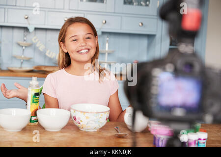Pre-teen girl video blogging in the kitchen smiles to camera - Stock Photo